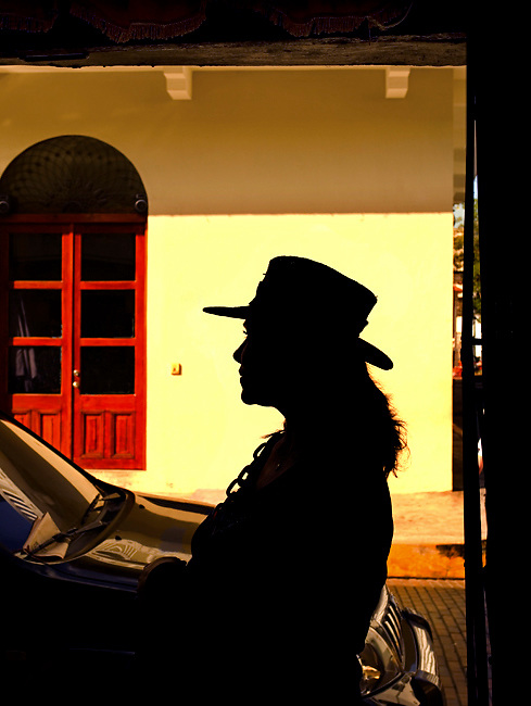 Woman resident of Casco Viejo (the old quarter) in Panama City is silhouetted against a yellow wall.