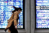 FRA03 TOKIO (JAPÓN) 2/3/2011.- Una mujer camina frente a un tablero electrónico con los índices de la Bolsa de Tokio (Japón), que hoy, miércoles 02 de marzo de 2011, sufrió su mayor caída en seis meses al perder más del 2 por ciento, en medio de la inquietud por la subida de los precios del petróleo y su posible impacto en la recuperación económica global..El selectivo Nikkei retrocedió 261,65 puntos, un 2,43 por ciento, y quedó en 10.492 unidades, con lo que prácticamente anuló las ganancias que había acumulado en las últimas tres sesiones. EFE/FRANCK ROBICHON