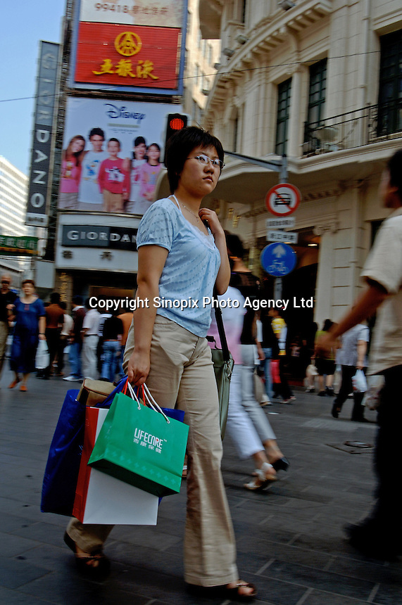 A woman shopped in Nanjing Lu. The street attracts hundreds of thousands of consumers and is home to many of the world's largest brand names..25 Sept 05