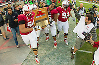 Stanford, CA -- November 23, 2013:  Stanford's David Yankey, Shayne Skov, and Khalil Wilkes carry the Axe after winning its game against Cal at Stanford Stadium. Stanford defeated Cal 63-13.