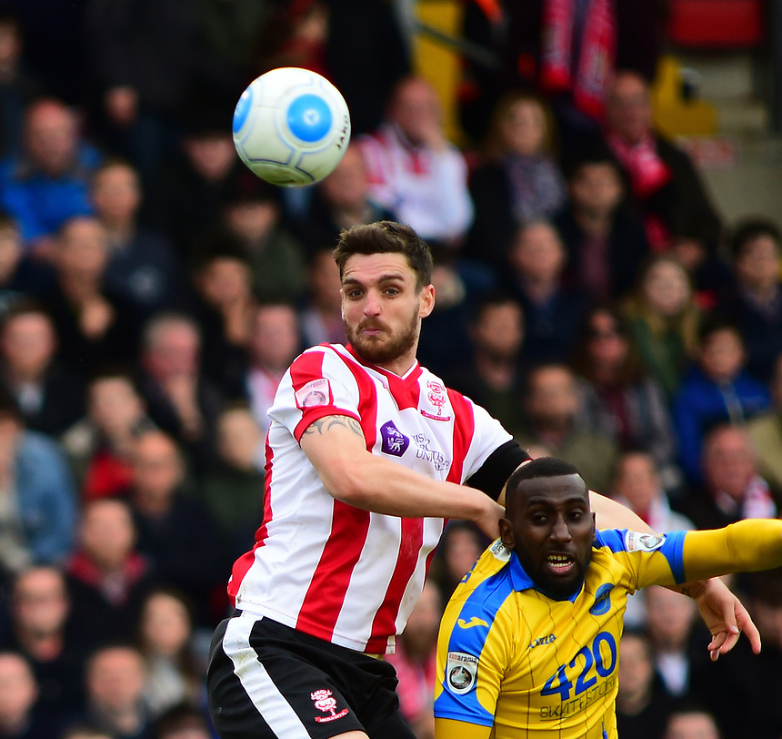 Lincoln City's Luke Waterfall vies for possession with Torquay United's Lathaniel Rowe-Turner<br /> <br /> Photographer Andrew Vaughan/CameraSport<br /> <br /> Vanarama National League - Lincoln City v Chester - Tuesday 11th April 2017 - Sincil Bank - Lincoln<br /> <br /> World Copyright &copy; 2017 CameraSport. All rights reserved. 43 Linden Ave. Countesthorpe. Leicester. England. LE8 5PG - Tel: +44 (0) 116 277 4147 - admin@camerasport.com - www.camerasport.com