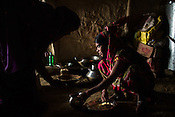 Lal Chuni Devi helps Srikanthi Devi with her lunch in their kitchen in Ramgarwa village in Raxaul district in Bihar, India.