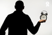 Silhouette of man holding alarm clock (Licence this image exclusively with Getty: http://www.gettyimages.com/detail/sb10068346bd-001 )