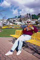 White Rock, BC, British Columbia, Canada - Woman sitting on Bench and reading a Book (Model Released)