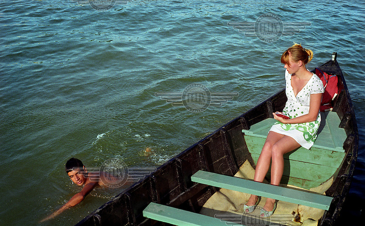 A woman sits in a boat as a boy swims past.
