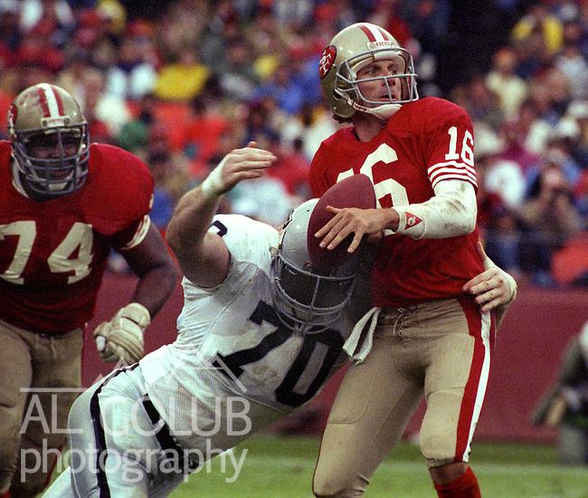 San Francisco 49ers vs Los Angles Raiders at Candlestick Park Sunday, November 13, 1988..Raiders Beat 49ers 9-3.Los Angles Raider linebacker Scott Davis (70) grabs San Francisco 49ers quarterback Joe Montana (16) ..