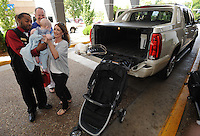 NWA Democrat-Gazette/ANDY SHUPE<br /> Mitch Collins (top) and Stacy Prout (right) of Conway smile Friday, Sept. 4, 2015, as Tony Blackburn, bell and ballet manager for The Chancellor Hotel, Friday, Sept. 4, 2015, returns their 4-month-old son, Colt Collins, while helping them load their belongings into the hotel ahead of today's season-opening football game at the University of Arkansas. The couple have become very close friends with Blackburn after coming to the hotel for games over the years and enjoyed catching up as they moved into their room.