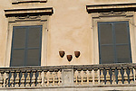 Shutters and flower pots on a wall in the Parione district of Rome.
