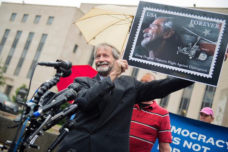 UNITED STATES - MAY 21: Doug Hughes holds a poster of a stamp made in likeness during a news conference outside of the E. Barrett Prettyman Federal Courthouse, May 21, 2015, after pleading not guilty to six counts regarding his landing of a gyrocopter on the West Lawn of the Capitol in April. (Photo By Tom Williams/CQ Roll Call)