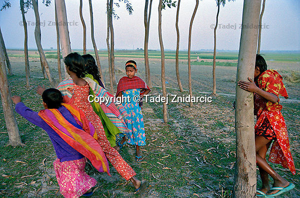 Rupali Khatun watches other girls from her class play behind their village of Kalinagar. (Photo by Tadej Znidarcic)