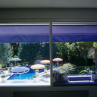 View from the living room to the swimming pool surrounded by brightly coloured parasols