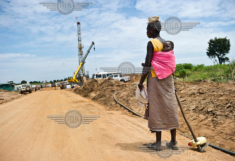 A woman carrying a child on her way to her field passes the entrance to Kigogole oil field, drilling site of Tullow Oil. As the site expands, the local population often have no other choice but to give up their land.