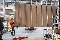 Workers manuever a wall in place for modular housing in the Capsys factory in the Brooklyn Navy Yard in New York on Thursday, February 11, 2016. Because of rising rents and the need for a specialized space the factory will be closing down after after this job, housing for the Nehemiah Spring Creek development. Steiner Studios, another tenant at the Brooklyn Navy Yard will be taking over the space. (© Richard B. Levine)