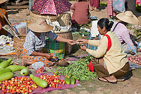 "Myanmar, Burma.  Woman Buying Vegetables,  Local ""Five-Day"" Market, Inle Lake, Shan State."
