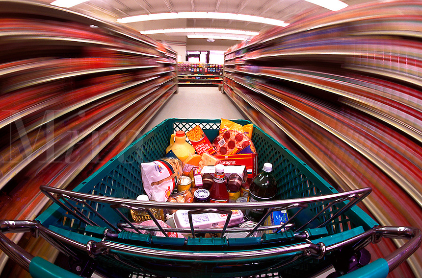 Shopping cart with groceries rushing through a grocery food store.