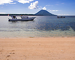 Dive boats are moored off the beach at Siladen Resort and Spa, on Siladen Island in the Bunaken National Park, off North Sulawesi, Indonesia.  In the distance are Bunaken Island and volcanic Manado Tua.