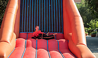 Katie Gibbs '15 and Tyler Steimel '14 try out the velcro wall. Occidental College celebrates Homecoming and Family Weekend on Saturday, Oct. 14, 2017 at Oswald's Homecoming Party in the Academic Quad, featuring games, activity booths, a pub and food.<br /> (Photo by Marc Campos, Occidental College Photographer)
