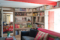 Rustic shelves give character to the book room which connects with the sitting room and has red lacquer painted window shutters and beams