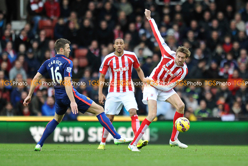 Peter Crouch of Stoke City vies for the ball with Michael Carrick of Manchester United - Stoke City vs Manchester United - Barclays Premier League Football at the Britannia Stadium, Stoke-on-Trent - 01/01/15 - MANDATORY CREDIT: Greig Bertram/TGSPHOTO - Self billing applies where appropriate - contact@tgsphoto.co.uk - NO UNPAID USE