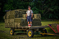 Sam Bigham stands on a trailer loaded with fresh hay recently baled on his family's Westerville, OH, farm. Bigham's family has owned the farm since 1920 but recently signed a contingency contract to sell the land to a housing developer. It is the last working farm in the city.
