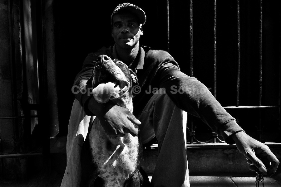 A Cuban man poses for a picture with his amstaff dog during a sunny morning in Havana, Cuba, 9 February 2009.