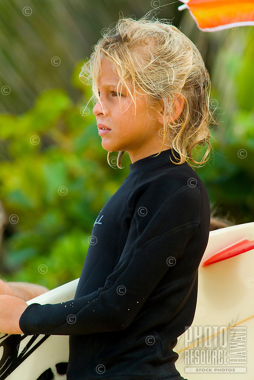 Close-up of a young blond boy wearing a wetsuit holding a surfboard on the north shore of Oahu