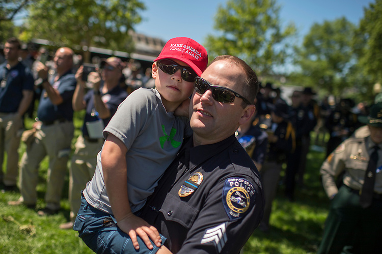 UNITED STATES - MAY 15: Sgt. Jason Coke of the Port of Seattle Police, and his son Reed, 9, listen to President Donald Trump address the 36h Annual National Peace Officers' Memorial Service on the West Front lawn of the Capitol on May 15, 2017. (Photo By Tom Williams/CQ Roll Call)