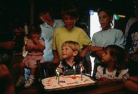 "Candles are lit on the cake and his family surrounds Jake Colson while singing ""Happy Birthday."""