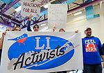 """Westbury, New York, USA. January 15, 2017. LI Activists group members bring a large banner and signs, and one wears """"FEEL THE BERN"""" T-shirt to the """"Our First Stand"""" Rally against Republicans repealing the Affordable Care Act, ACA, taking millions of people off health insurance, making massive cuts to Medicaid, and defunding Planned Parenthood. Hosts were Reps. K. Rice (Democrat - 4th Congressional District) and T. Suozzi (Dem. - 3rd Congress. Dist.)."""