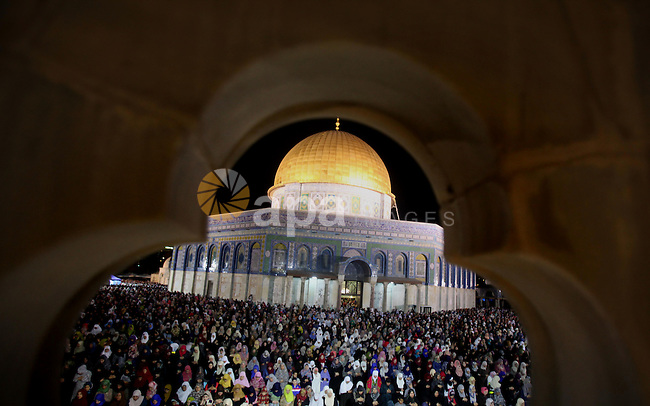 Palestinian muslim worshipers take part in Laylat Al Qadr prayers or Night of Power, in which the Muslim holy book of Koran was revealed to Prophet Mohammad by Allah on the 27th day of the holy fasting month of Ramadan in front of the Dome of the Rock, in the Al Aqsa Mosque compound in Jerusalem during Ramadan July 1, 2016. Photo by Mahfouz Abu Turk