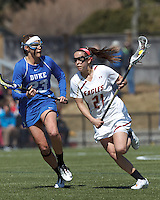 Boston College midfielder Caroline Margolis (21) on the attack as Duke University defender Taylor Virden (23) defends.Boston College (white) defeated Duke University (blue), 10-9, on the Newton Campus Lacrosse Field at Boston College, on April 6, 2013.