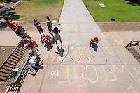 Occidental College's class of 2020 and their O-Team leaders write their names and where they are from in chalk on the sidewalk in front of Thorne Hall during Orientation, Aug. 29, 2016.<br />