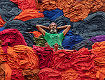 Cloth worker takes a break from loading lorry with colourful materials by Abdul Momin
