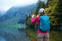 A hiker makes a photo with her phone of fall colors at the Seealpsee in the Alpstein, Switzerland.
