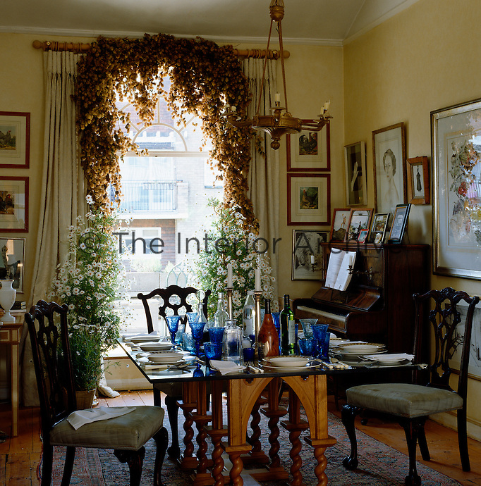 In the dining room, potted Marguerites and a garland of dried flowers frame the tall window