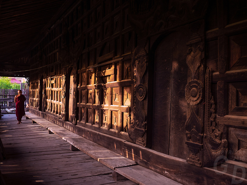 A Buddhist Monk walking through an old Teakwood Monastery in Mandaly, Myanmar, Burma.