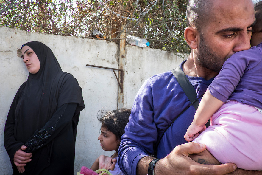 Mahmoud, with his wife,  Jihan, holding baby Luna, one of her four children, locked outside of Moria Camp in Lesbos. Abdo said they are all Syrians who lost their documents.  Jihan was crying tears of frustration after being sent back and forth between the two registration camps in Lesbos, Greece. One camp is exclusively for Syrians while the other, more crowded camp is for all other immigrants. Lacking Syrian passports, they were bounced back and forth between the two camps that are several kilometers apart.