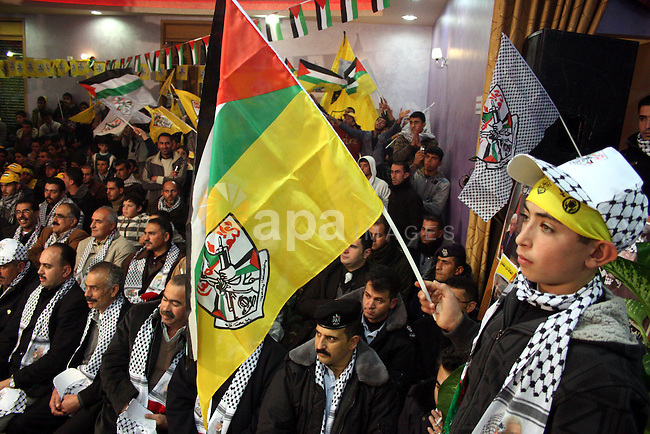 Palestinian supporters of Fatah wave the movement's flag and Palestinian flag during a rally marking the 46th anniversary of the secular party's creation in the village of Halhoul near the West Bank city of Hebron on January 01, 2011.. Photo by Najeh Hashlamoun