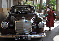 A monk passes a vintage Mercedes car outside the Strand hotel in Rangoon, Burma. Nov 2008.