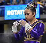 The SEC National Gymnastic Championship was held on Saturday March 24 at Chaifetz Arena on the Saint Louis University campus. Sarah Finnegan of LSU blows excess chalk from her hands before competing on the uneven bars.<br />