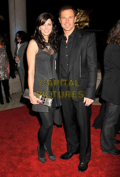 KAREN FAIRCHILD & JIMI WESTBROOK.BMI's 56th Annual Country Awards held at BMI Music Row, Nashville, Tennessee, USA..November 11th, 2008.full length black suit grey gray dress clutch bag .CAP/ADM/LF.©Laura Farr/AdMedia/Capital Pictures.