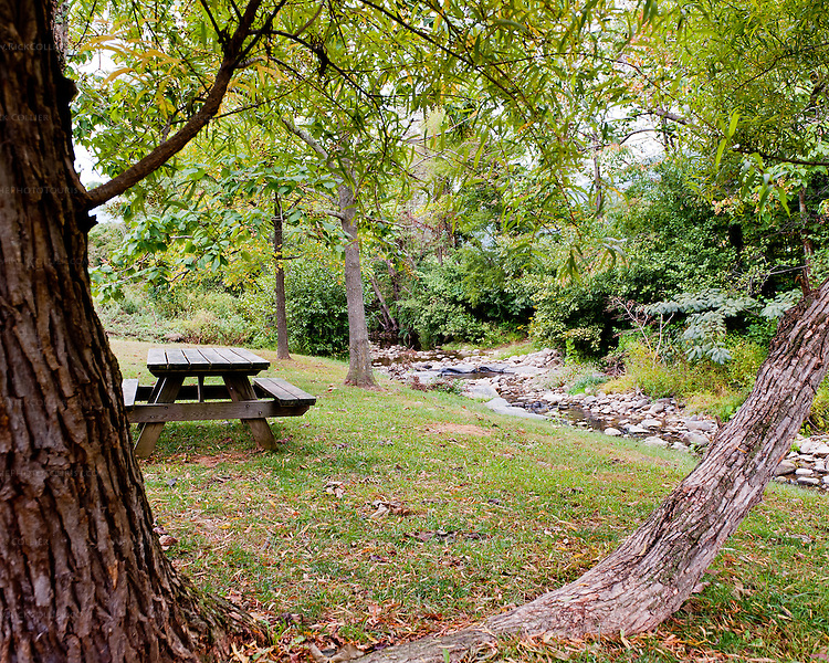 The south fork of the Rockfish River borders the lawn dotted with picnic tables, chairs, and benches at Wintergreen Winery.