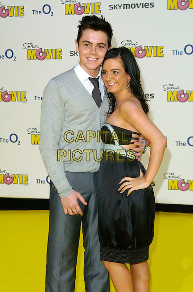"RAY QUINN & GUEST.""The Simpsons Movie"" UK premiere at the Vue O2 Arena cinema, London, England..July 25th, 2007.full length grey gray trousers cardigan black strapless dress hand on hip silver 3/4.CAP/CAN.©Can Nguyen/Capital Pictures"