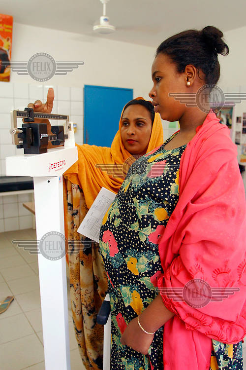 A health worker weighs a pregnant woman during a general check-up at a health centre.