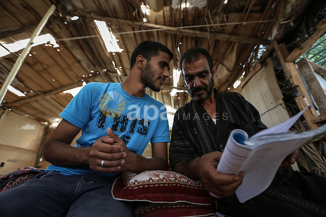 The father of Fadi al-Shami, 21, a Palestinian blind youth, helps him in studying at his home in Central Gaza Strip on Aug 17, 2013. al-Shami lost his sight after he was injured by an Israeli airstrike next to his family home at al-Musaddar village in central Gaza Strip during the Gaza–Israel conflict in 2006. Photo by Mahmoud Hamda