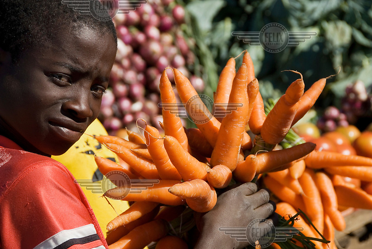 A boy holds a bunch of carrots at a vegetable market.