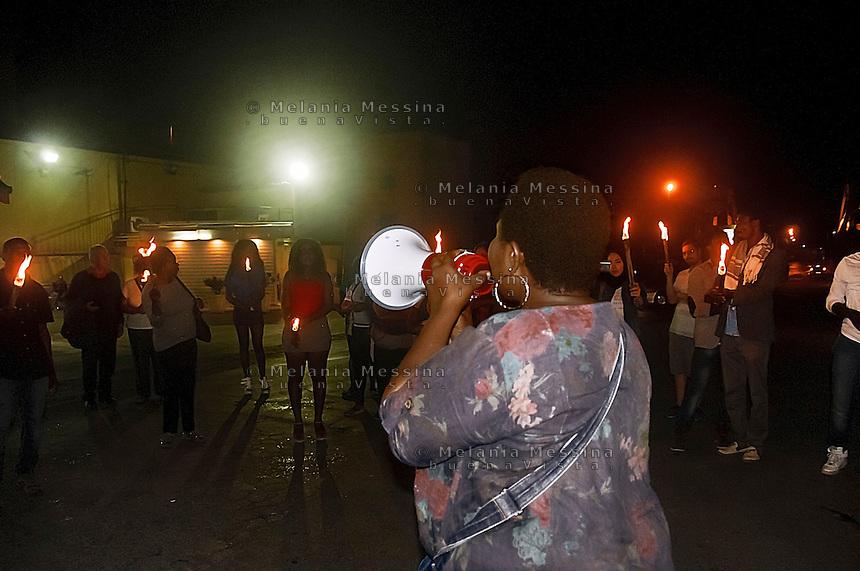 Osas vice presidente dell'associazione &quot;Donne del Benin&quot; durante una fiaccolata contro la tratta di esseri umani fa un appello ad un gruppo di minorenni nigeriane sulla strada offrendo loro aiuto per uscire dal racket della prostituzione, le ragazze hanno preso la fiaccola.<br /> Osas, vice president of &quot;Women from Benin association&quot; during a march against human trafficking, offers help to a group of Nigerian teenagers prostitutes, the girls for a short  while joined the activist holding the torches
