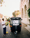 SRI LANKA, Asia, Galle, Young man carrying flowers in front of the Amangalla Hotel in Galle.