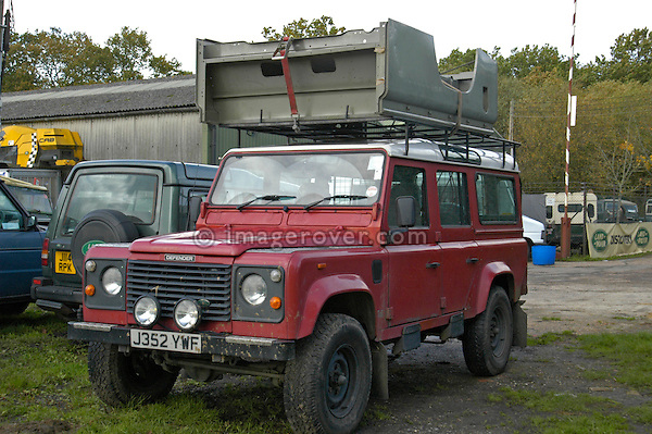 A complete Land Rover 110 HT rear body loaded onto the large roof rack of a Land Rover Defender 110 Station Wagon. --- No releases available. Automotive trademarks are the property of the trademark holder, authorization may be needed for some uses.