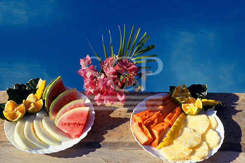 Buzios, Rio de Janeiro State, Brazil. Two mouthwatering and delicious plates of exotic fruits next to a swimming pool.